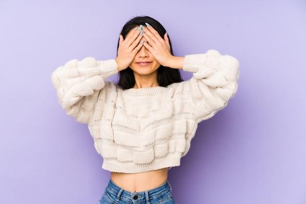Jovem chinesa isolada em um fundo roxo cobre os olhos com as mãos, sorrisos à espera de uma surpresa.