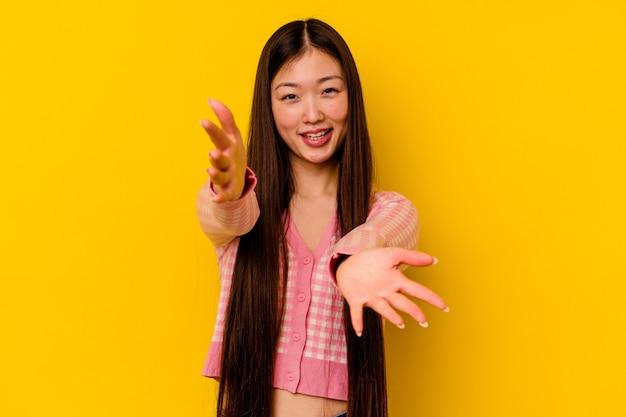 Jovem chinesa isolada em uma parede amarela se sente confiante dando um abraço na câmera