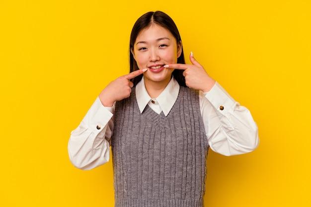 Jovem chinesa isolada em uma parede amarela sorrindo, apontando o dedo para a boca