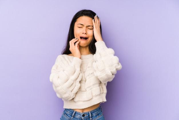 Jovem chinesa isolada em uma parede roxa, chorando e chorando desconsoladamente.