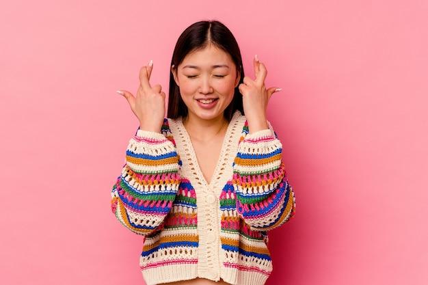 Jovem chinesa isolada na rosa cruzando os dedos por ter sorte