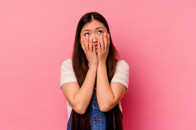 Jovem chinesa isolada no fundo rosa, chorando e chorando desconsoladamente.