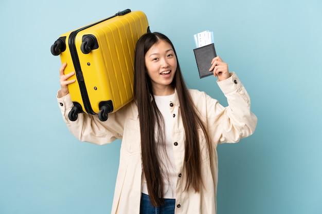 Jovem chinesa isolada sobre férias com mala e passaporte