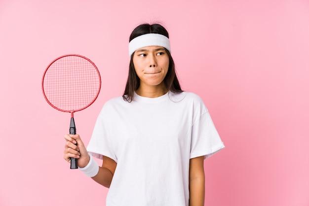 Jovem chinesa jogando badminton em uma parede rosa confusa, sente-se duvidoso e inseguro.