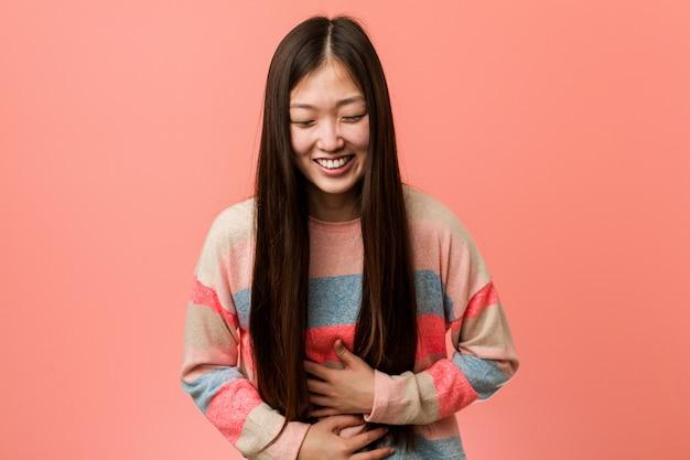 Jovem chinesa legal ri alegremente e se diverte mantendo as mãos no estômago.
