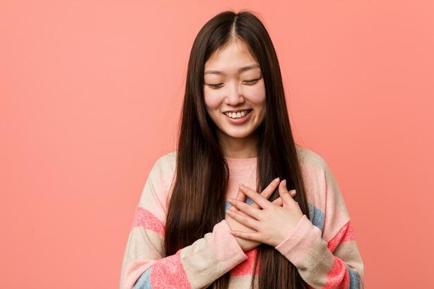 Jovem chinesa legal rindo mantendo as mãos no coração, de felicidade.