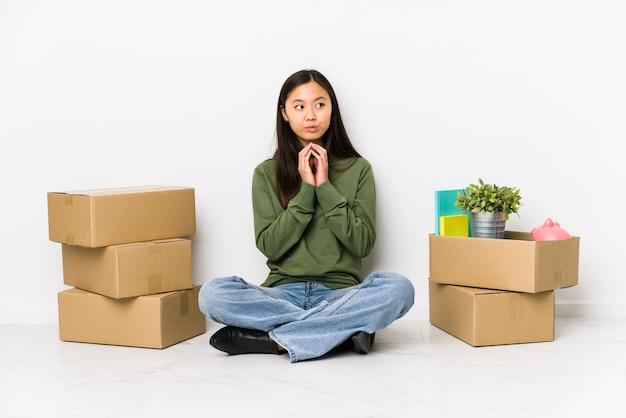Jovem chinesa, movendo-se para uma nova casa, inventando o plano em mente, criando uma idéia.