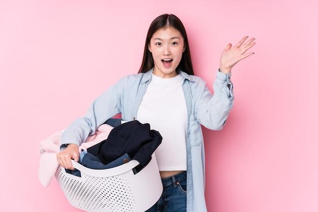 Jovem chinesa pegando roupas sujas isolada recebendo uma agradável surpresa, animada e levantando as mãos.