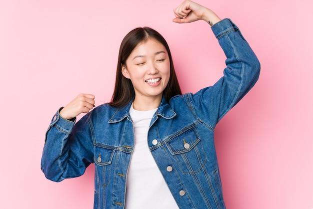 Jovem chinesa posando em rosa isolada comemorando um dia especial, pula e levanta os braços com energia.