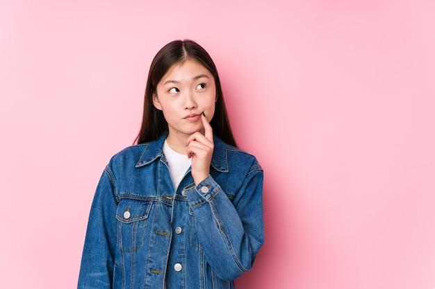 Jovem chinesa posando em um espaço rosa isolado, olhando de soslaio com expressão duvidosa e cética.