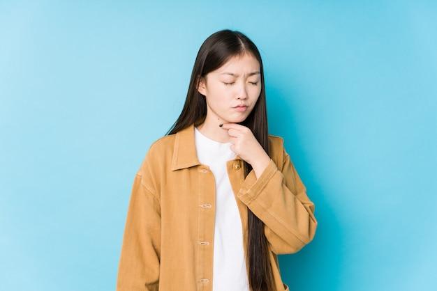 Jovem chinesa posando em uma parede azul sofre dor na garganta devido a um vírus