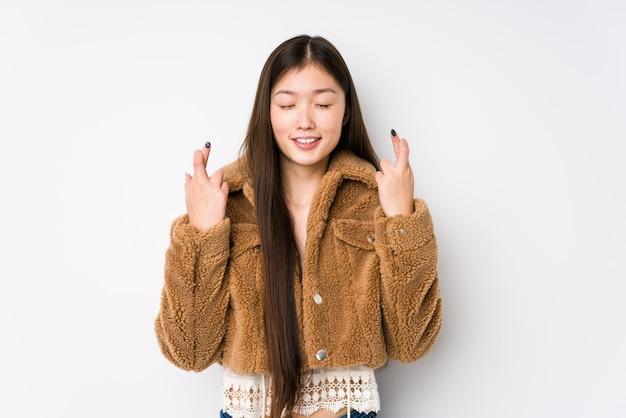 Jovem chinesa posando em uma parede branca, cruzando os dedos