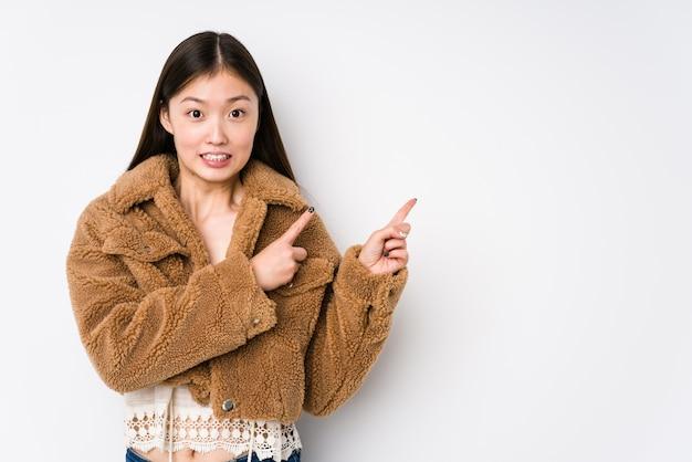 Jovem chinesa posando em uma parede branca isolada chocada apontando com o dedo indicador para um espaço de cópia.