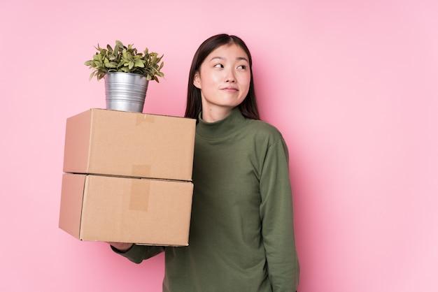 Jovem chinesa segurando caixas isoladas, sonhando em alcançar objetivos e propósitos