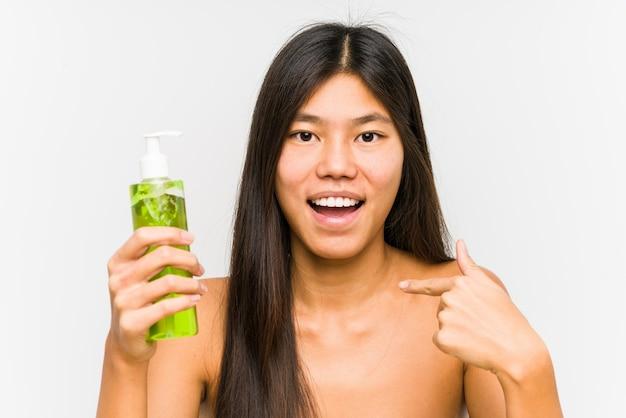 Jovem chinesa segurando um creme hidratante com aloe vera surpreendeu apontando para si mesmo, sorrindo amplamente.