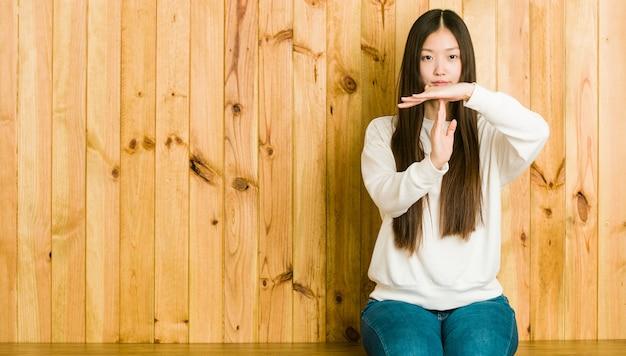 Jovem chinesa sentada em um lugar de madeira, mostrando um gesto de tempo limite.
