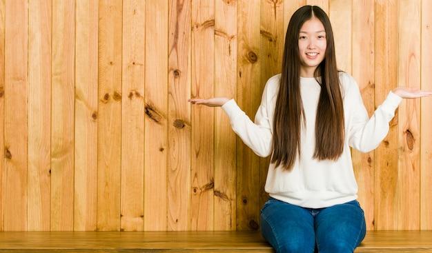 Jovem chinesa sentado em um lugar de madeira faz escala com os braços, sente-se feliz e confiante.