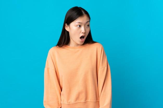 Jovem chinesa sobre azul isolado, fazendo o gesto de surpresa enquanto olha para o lado