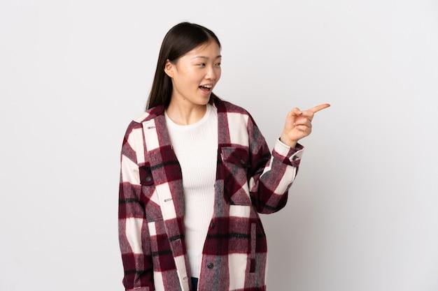 Jovem chinesa sobre dedo apontando branco isolado para o lado e apresentar um produto
