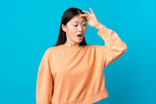 Jovem chinesa sobre parede azul isolada, fazendo o gesto de surpresa enquanto olha para o lado