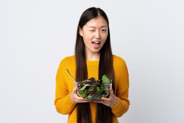 Jovem chinesa sobre parede branca isolada, segurando uma tigela de salada enquanto piscava