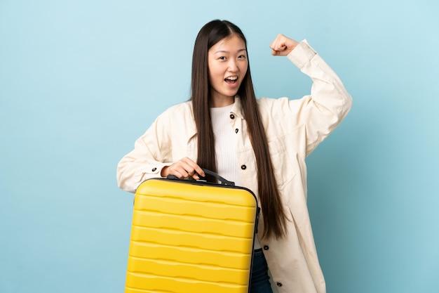 Jovem chinesa sobre parede em férias com mala de viagem