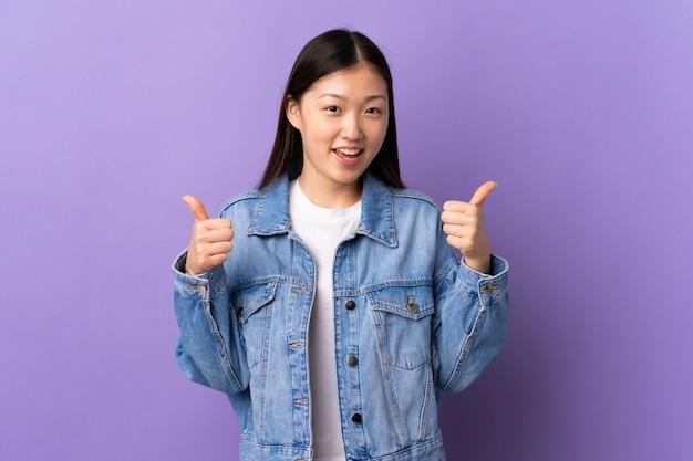 Jovem chinesa sobre roxo isolado dando um polegar para cima gesto