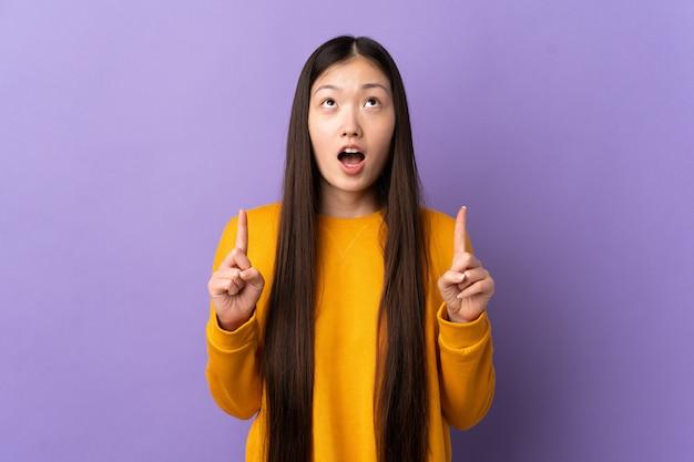 Jovem chinesa sobre roxo isolado surpreso e apontando para cima