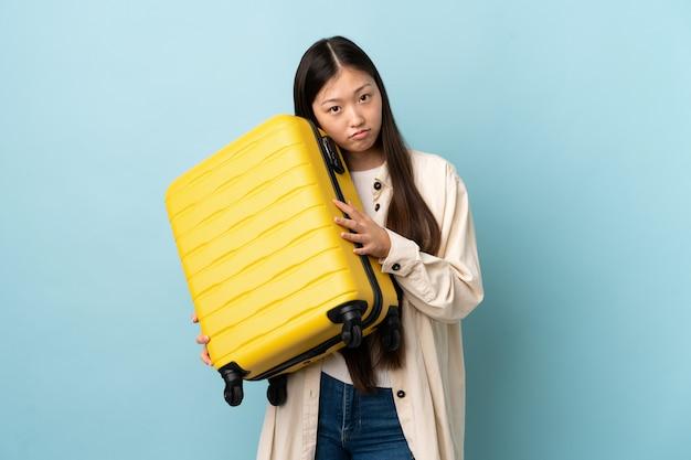Jovem chinesa sobre um muro isolado em férias com mala de viagem e infeliz