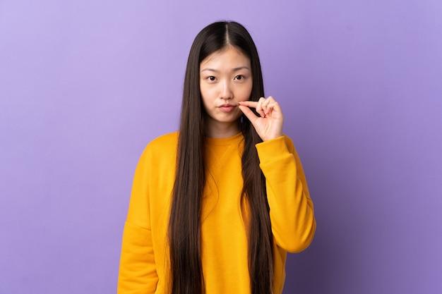 Jovem chinesa sobre um roxo isolado mostrando um gesto de silêncio