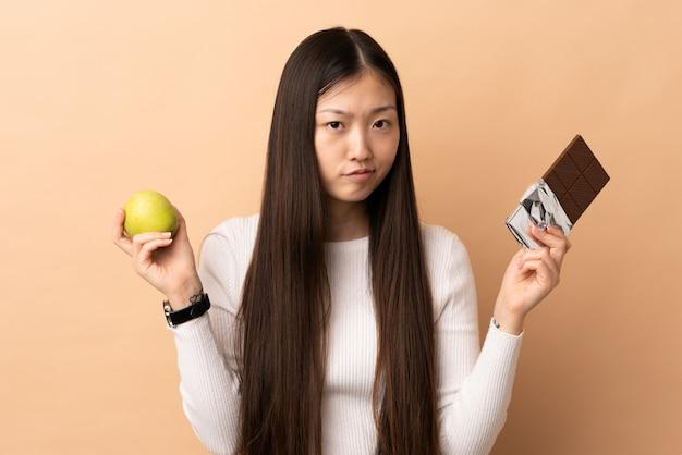 Jovem chinesa tendo dúvidas enquanto toma uma tablete de chocolate em uma mão e uma maçã na outra
