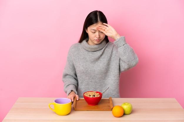 Jovem chinesa tomando café da manhã em uma mesa com uma expressão cansada e doente