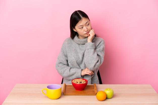 Jovem chinesa tomando café da manhã em uma mesa com uma expressão cansada e entediada
