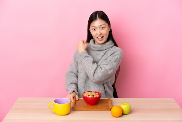 Jovem chinesa tomando café da manhã em uma mesa comemorando uma vitória