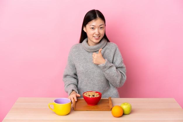 Jovem chinesa tomando café da manhã em uma mesa, dando um polegar para cima gesto