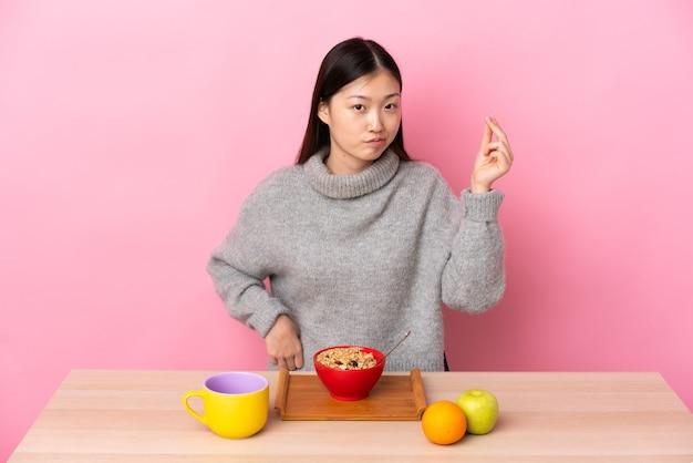 Jovem chinesa tomando café da manhã em uma mesa fazendo gesto italiano