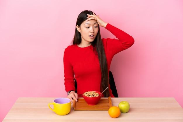 Jovem chinesa tomando café da manhã em uma mesa, fazendo o gesto de surpresa enquanto olha para o lado