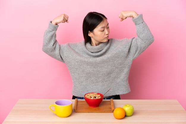Jovem chinesa tomando café da manhã em uma mesa fazendo um gesto forte