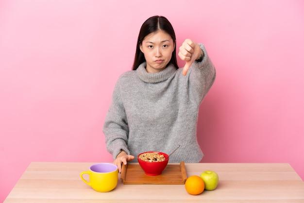 Jovem chinesa tomando café da manhã em uma mesa mostrando o polegar para baixo com expressão negativa
