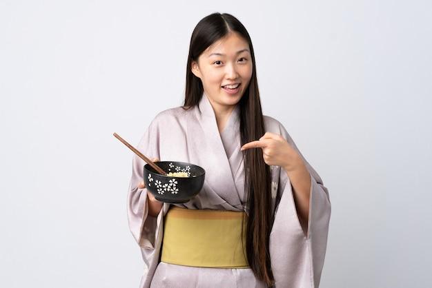 Jovem chinesa usando quimono sobre um fundo branco isolado e apontando-o enquanto segura uma tigela de macarrão com pauzinhos