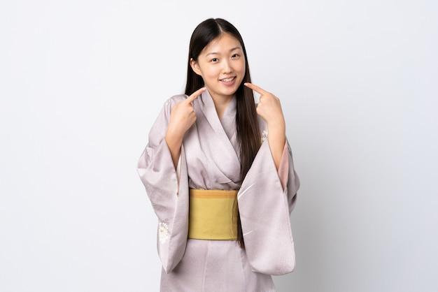 Jovem chinesa vestindo quimono dando um polegar para cima gesto