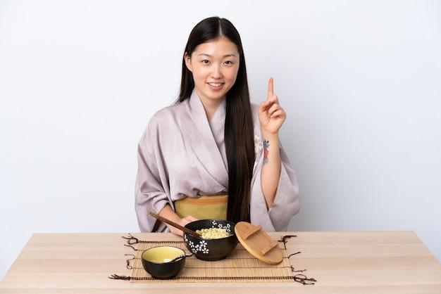 Jovem chinesa vestindo quimono e comendo macarrão apontando para cima uma ótima idéia