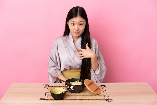 Jovem chinesa vestindo quimono e comendo macarrão apontando para si mesmo