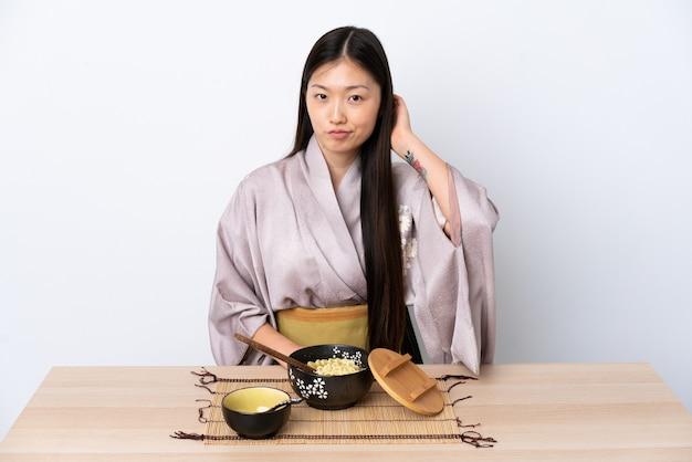 Jovem chinesa vestindo quimono e comendo macarrão com dúvidas