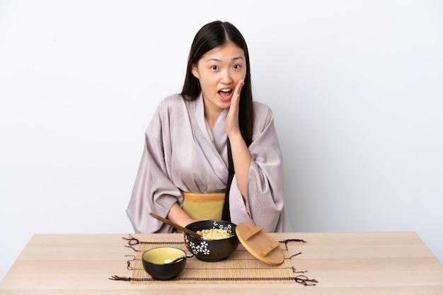 Jovem chinesa vestindo quimono e comendo macarrão com expressão facial surpresa e chocada