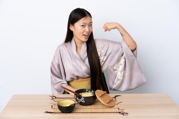 Jovem chinesa vestindo quimono e comendo macarrão, fazendo um gesto forte