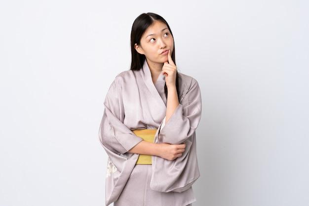 Jovem chinesa vestindo quimono tendo dúvidas enquanto olha para cima