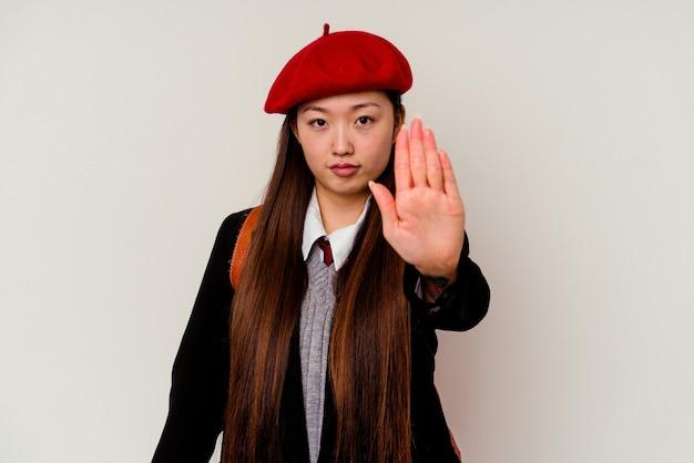 Jovem chinesa vestindo um uniforme escolar em pé com a mão estendida, mostrando o sinal de pare, impedindo você.
