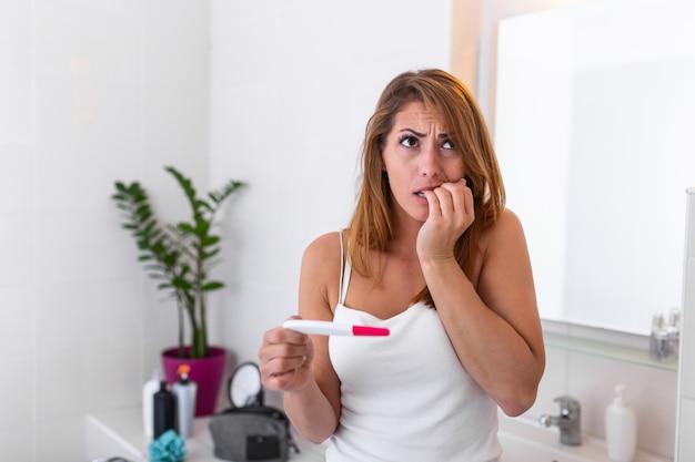 Jovem chocada com gravidez indesejada, olhando o teste no banheiro.