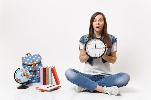 Jovem chocada e assustada estudante em roupas jeans segurando um despertador sentado perto do globo, mochila, livros escolares isolados